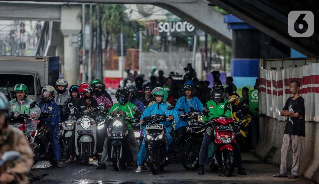Pengendara sepeda motor memenuhi ruas jalan ketika berteduh di kolong Fly Over Cawang, Jakarta, Selasa (17/12/2019). Perilaku tersebut selain menimbulkan ketidaknyamanan pengguna jalan lainnya, juga memicu kemacetan. (Liputan6.com/Faizal Fanani)