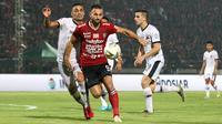 Striker Bali United, Ilija Spasojevic, berebut bola dengan bek Madura United, Jaimerson Xavier, pada laga Liga 1 2019 di Stadion Kapten I Wayan Dipta, Bali, Minggu (22/12). Bali kalah 0-2 dari Madura. (Bola.com/Aditya Wany)