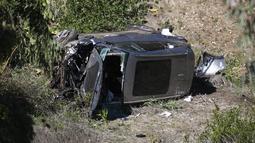 Sebuah crane digunakan untuk mengangkat mobil pegolf Tiger Woods setelah kecelakaan di Rancho Palos Verdes, California, pinggiran Los Angeles, Selasa (23/2/2021). Kendaraan yang dibawa Woods keluar dari jalan raya dan terguling ke lereng sebelum berhenti di dasar jurang. (AP Photo/Mark J. Terrill)