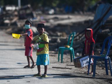 Anak-anak yang terkena dampak gempa meminta sumbangan pada pengguna jalan yang melintas di Donggala, Sulawesi Tengah, Jumat (5/10). Akibat terlambatnya pasokan bantuan, mereka terpaksa meminta sumbangan hingga turun ke jalan. (AFP PHOTO / Jewel SAMAD)