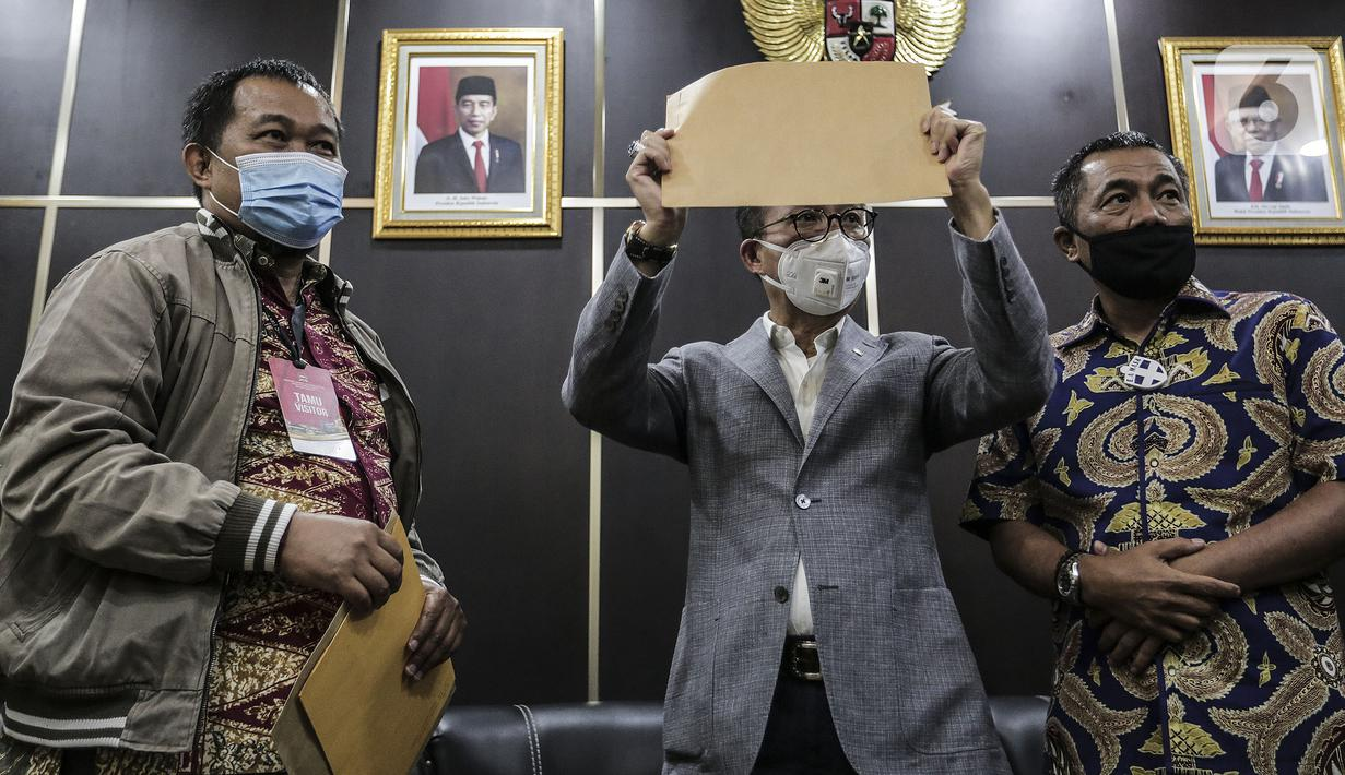 Koordinator MAKI Boyamin Saiman (kiri) menyerahkan salinan surat jalan Djoko Tjandra kepada Ketua Komisi III DPR Herman Herry di Kompleks Parlemen, Jakarta, Selasa (14/7/2020). Komisi III DPR diminta mengawasi polemik buron kasus korupsi hak tagih Bank Bali tersebut. (Liputan6.com/Johan Tallo)