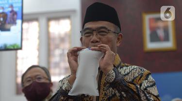 Menko PMK Muhadjir Effendy memperagakan alat GeNose C19 buatan Universitas Gadjah Mada (UGM) di Kementerian PMK, Jakarta, Kamis (7/1/2021). Alat itu diserahkan oleh Menteri Riset dan Teknologi Bambang Brodjonegoro, Kamis (7/1/2021). (merdeka.com/Imam Buhori)