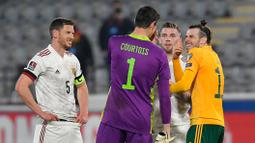 Kiper Belgia, Thibaut Courtois, bercengkrama dengan penyerang Wales, Gareth Bale, pada laga Kualifikasi Piala Dunia 2022 di Stadion Den Dreef, Kamis (25/3/2021). Belgia menang dengan skor 3-1. (AFP/John Thys)
