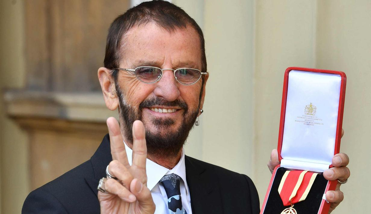 Ringo Starr berpose di Istana Buckingham, di London, Inggris (20/3). Mantan drummer The Beatles ini mendapat gelar kebangsawanan dari Pangeran William. Ia diberi gelar 'Sir' atas jasanya dalam dunia musik. (John Stillwell / Pool Photo via AP)