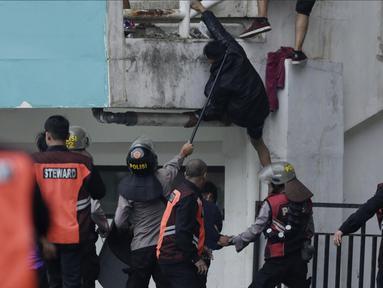 Polisi mengusir suporter Persita Tangerang yang masuk ke lapangan saat melawan Kalteng Putra pada laga Liga 2 di Stadion Pakansari, Jawa Barat, Selasa (4/12). Kalteng menang 2-0 atas Persita. (Bola.com/M. Iqbal Ichsan)