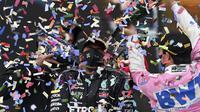 Pembalap Mercedes, Lewis Hamilton disemprotkan sampanye oleh pembalap Racing Point, Sergio Perez saat merayakan Juara Dunia Formula 1 2020 di sirkuit balap Istanbul Park di Istanbul, Minggu (15/11/2020). Ini jadi gelar ke-7 yang berhasil dicapai sepanjang karirnya. (Ozan Kose/Pool via AP)