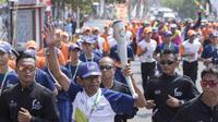 Legenda balap sepeda Indonesia, Sutiyono, membawa obor pada pawai Asian Games di Bandar Lampung, Rabu (8/8/2018). (Bola.com/Reza Bachtiar)