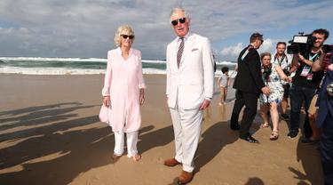 Pangeran Charles bersama istrinya, Duchess of Cornwall Camilla berjalan di atas pasir pantai saat mengunjungi Broadbeach di Gold Coast, Australia, Kamis (5/4). Istri Pangeran Charles itu terlihat berjalan tanpa alas kaki. (Mark Metcalfe/POOL/AFP)