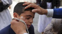 Seorang pria Yaman mengoleskan kosmetik tradisional Kohl ke kelopak mata remaja selama bulan puasa Ramadhan di Masjid Sanaa (16/4/2021).  Umat Muslim di Yaman percaya bahwa kohl atau celak mampu membersihkan dan melindungi mata dari berbagai penyakit. (AFP/ Mohammed Huwais)