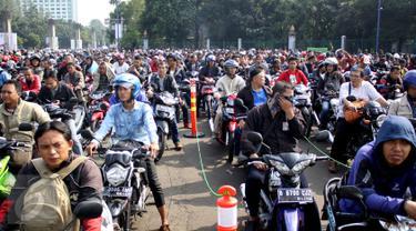 Ribuan pemotor mengantre ketika mendaftarkan diri sebagai pengojek GrabBike di Senayan, Jakarta, Rabu (12/8/2015). Lowongan kerja sebagai pengojek online tersebut merupakan peluang kerja baru bagi masyarakat. (Liputan6.com/Gempur M Surya)
