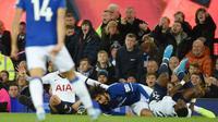 Reaksi pemain Everton, Andre Gomes (tengah), setelah ditekel pemain Tottenham Hotspur, Son Heung-min, pada laga di Goodison Park, Minggu (3/11/2019). (AFP/Oli Scarff)