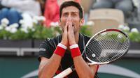 Reaksi petenis Serbia, Novak Djokovic saat melawan petenis Italia Marco Cecchinato pada perempatfinal Prancis Terbuka 2018 di stadion Roland Garros, Selasa (5/6). Djokovic dikalahkan petenis non-unggulan dalam duel empat set. (AP/Christophe Ena)