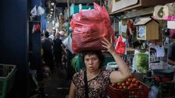 Pembeli membawa belanjaan menggunakan kantong plastik di Pasar Senen, Jakarta, Rabu (8/1/2020). Gubernur DKI Jakarta Anies Baswedan mengeluarkan pergub tentang larangan kantong plastik sekali pakai di mal, swalayan, hingga pasar. Larangan ini berlaku mulai Juli 2020. (Liputan6.com/Faizal Fanani)