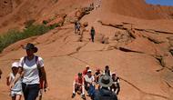 Wisatawan mendaki Uluru yang juga dikenal sebagai Batu Ayers di Taman Nasional Uluru-Kata Tjuta, utara Australia, Jumat (25/10/2019). Kawasan wisata bukit batu Uluru dipenuhi pengunjung, lantaran hari ini merupakan hari terakhir sebelum larangan pendakian diberlakukan. (SAEED KHAN / AFP)