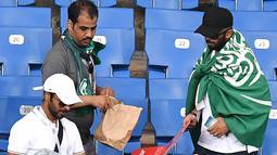 Suporter Arab Saudi mengumpulkan sampah di tribun seusai laga melawan Uruguay pada pertandingan kedua Grup A Piala Dunia 2018 di Rostov Arena, Rabu (20/6). Kalah 0-1, Arab Saudi menjadi tim kedua yang tersingkir setelah Maroko. (AFP/JOE KLAMAR)