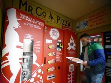 Seorang pria mengambil pesanannya di mesin penjual pizza otomatis, yang pertama dari jenisnya di pusat kota Roma, pada 29 April 2021. Mesin penjual otomatis ini mampu menguleni adonan, membumbui, memasak, dan menyajikan pizza dalam kotak karton hanya dalam waktu tiga menit. (Filippo MONTEFORTE/AFP)
