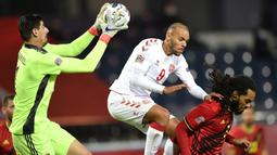 Kiper Belgia, Thibaut Courtois, berusaha menangkap bola saat menghadapi Denmark pada laga lanjutan UEFA Nations League di Stadion Den Dreef, Kamis (19/11/2020) dini hari WIB. Belgia menang 4-2 atas Denmark. (AFP/John Thys)