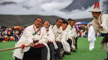 Para kontestan mengikuti kompetisi tarik tambang di Wilayah Damxung, Daerah Otonom Tibet, China, 10 Agustus 2020. Dengan pakaian tradisional, para penggembala dari sejumlah desa di Wilayah Damxung berpartisipasi dalam permainan tradisional itu. (Xinhua/Purbu Zhaxi)