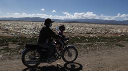 Pengendara sepeda motor melewati sampah di tepian Danau Uru Uru dekat Oruro, Bolivia, Kamis (25/3/2021).  Mayoritas sampah rumah tangga ini terbawa dari aliran sungai yang bermuara di danau ini. (AP Photo / Juan Karita)