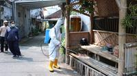 Petugas BPBD Kota Malang menyemprotkan disinfektan di kampung JA Suprapto III yang jadi salah satu klaster baru penyebaran Covid-19 (Liputan6.com/Zainul Arifin)