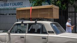Peti mati kardus berisi jenazah diletakkan di atas mobil sebelum dimakamkan di luar Rumah Sakit Teodoro Maldonado di Guayaquil, Senin (6/4/2020). Kehabisan peti mati, kota terbesar di Ekuador yang menjadi klaster wabah virus corona itu menggunakan kotak kardus untuk korban Covid-19. (AP/Luis Perez)