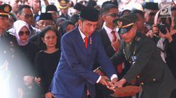 Presiden RI Joko Widodo atau Jokowi saat menimbun tanah ke liang lahat almarhumah Ani Yudhoyono di TMP Kalibata, Jakarta, Minggu (2/6/2019). Ani Yudhoyono meninggal dunia di National University Hospital Singapura pada 1 Juni 2019 karena kanker darah. (Fimela.com/Deki Prayoga)