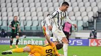 Pemain Juventus, Cristiano Ronaldo melewati adangan kiper Ferencvaros pada laga lanjutan Liga Champions 2020/2021. (MIGUEL MEDINA / AFP)