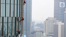 Pekerja membersihkan kaca gedung bertingkat di Jakarta, Jumat (26/02/2021). Berdasarkan data BP Jamsostek kasus kecelakaan kerja di Indonesia menurun 1,46 persen dengan catatan pada tahun 2020 mencapai 153.044 kasus dibandingkan 2019 sebanyak 155.327 kasus. (Liputan6.com/Fery Pradolo)