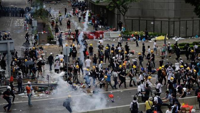 Pengunjuk rasa menghindari gas air mata yang ditembakan oleh polisi anti huru hara di luar gedung Dewan Legislatif, Hong Kong, Rabu (12/6/2019). Polisi Hong Kong telah menggunakan gas air mata ke arah ribuan demonstran yang menentang RUU ekstradisi yang sangat kontroversial. (AP Photo/Vincent Yu)
