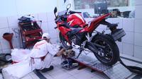 Mekanik bengkel Honda sedang melakukan service sepeda motor.