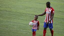 Jackson Martinez menggandeng anaknya Josue saat diperkenalkan sebagai pemain baru Atletico Madrid di Stadion Vicente Calderon, Madrid, Minggu (26/7/2015).(Reuters/Susana Vera)
