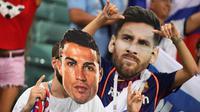 Suporter berpose memakai topeng bintang Portugal, Cristiano Ronaldo dan bintang Argentina, Lionel Messi sebelum laga babak perempat final Piala Dunia 2018 antara Rusia dan Kroasia di Stadion Olimpiade Fisht, Sabtu (7/7). (AFP PHOTO/Kirill KUDRYAVTSEV)