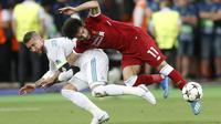 Striker Liverpool, Mohamed Salah, mendapat bantingan dari bek Real Madrid, Sergio Ramos pada laga final Liga Champions di Stadion NSC Olimpiyskiy, Kiev, Minggu (27/5/2018). Salah mengalami cedera bahu usai dilanggar Ramos. (AP/Efrem Lukatsky)