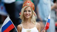 Suporter wanita tersenyum sambil memegang bendera Rusia sebelum pertandingan grup A Piala Dunia 2018 antara Rusia dan Arab Saudi di stadion Luzhniki di Moskow, (14/6). Dalam pertandingan ini, Rusia menang 5-0 atas Arab Saudi. (AP Photo/Antonio Calanni)