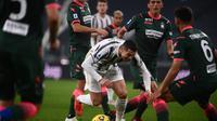 Cristiano Ronaldo dikepung oleh pemain Crotone pada laga lanjutan Liga Italia 2020/2021, Selasa (23/02/2021) dini hari WIB. (Marco BERTORELLO / AFP)