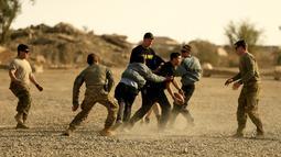 Tentara AS berlari untuk mengumpan bola kepada rekannya saat bermain American Football pada Thanksgiving di dalam pangkalan militer AS di Qayyara, selatan Mosul, Irak (24/141). (REUTERS/Thaier Al-Sudani)