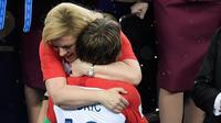 Presiden Kroasia, Kolinda Grabar-Kitarovic menghibur Kapten Kroasia, Luka Modric saat penyerahan medali dan trofi Piala Dunia 2018 di Luzhniki Stadium, Minggu (15/7). Kroasia harus puas menjadi runner-up seusai kalah 2-4 dari Prancis. (AFP/GABRIEL BOUYS)