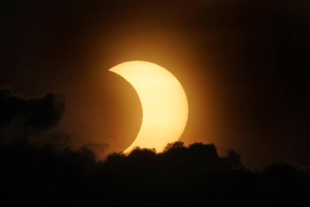 Matahari yang mengalami gerhana sebagian muncul dari balik awan saat terbit di atas Manhattan di New York, Kamis (10/6/2021). NASA menjelaskan beberapa wilayah Bumi yang bisa melihat fenomena tersebut yakni di bagian Kanada, Greenland, dan Rusia utara. (AP Photo/Seth Wenig)