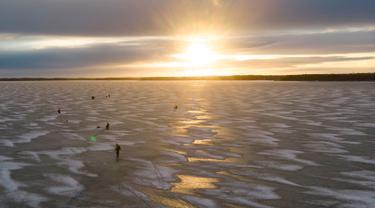 Pandangan udara menunjukkan para pria  sedang memancing di tengah Laut Bothnia yang membeku di dekat Vaasa, Finlandia, 28 Desember 2018. Memancing di laut beku merupakan hal yang ditunggu-tunggu oleh sebagian warga setempat. (OLIVIER MORIN / AFP)