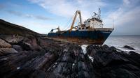 """Kapal kargo sepanjang 77 meter, MV Alta,  terjebak di atas batu di dekat Ballycotton, Cork, Irlandia, Selasa (18/2/2020). """"Kapal hantu"""" yang berlayar tanpa awak selama lebih dari satu tahun hanyut dan terbawa ke pantai selatan Irlandia menyusul sapuan Badai Dennis. (Cathal Noonan/AFP)"""