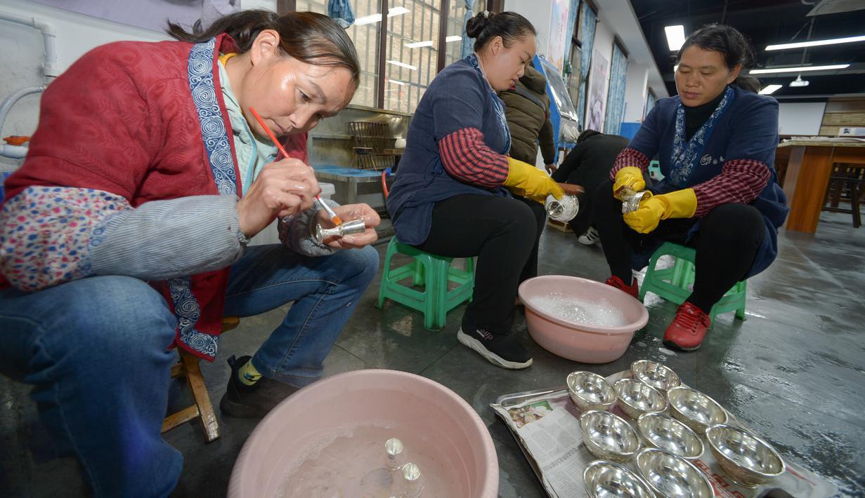 Para pekerja tampak sibuk di sebuah bengkel pembuatan kerajinan perak di Wilayah Danzhai, Provinsi Guizhou, China pada 17 November 2020. Menjelang perayaan Tahun Baru Etnis Miao, sebuah bengkel pembuatan produk perak memasuki musim puncak penjualan. (Xinhua/Yang Ying)