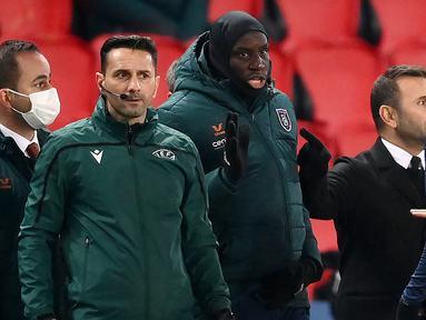 Asisten wasit ke-4, Sebastian Coltescu (kedua dari kiri) tampak di pinggir lapangan bersama striker Istanbul Basaksehir, Demba Ba (tengah) dalam laga lanjutan Liga Champions Grup H antara PSG melawan Istanbul Basaksehir di Parc des Princes Stadium, Selasa (8/12/2020). (AFP/Franck Fife)
