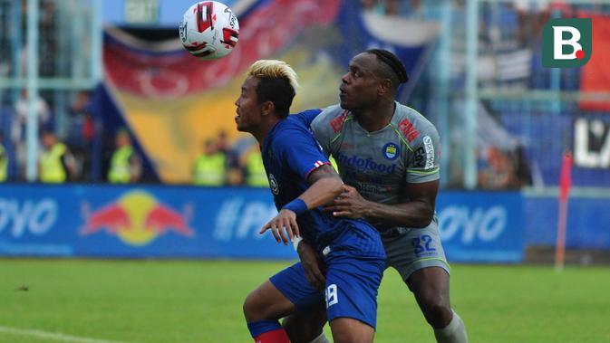 Duel sengit penyerang Arema FC, Kushedya Hari Yudo (biru), dan bek Persib Bandung, Victor Igbonefo, saat kedua tim bertemu di laga pekan kedua Shoppe Liga 1 2020 di Stadion Kanjuruhan, Minggu (8/3/2020). (Bola.com/Iwan Setiawan)