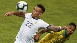 Pemain Brasil, Alex Sandro, duel udara dengan striker Argentina, Lautaro Martinez, pada laga Copa America 2019 di Stadion Mineirao, Rabu (3/7). Brasil menang 2-0 atas Argentina. (AP/Nelson Antoine)