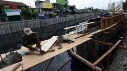 Pekerja melakukan pemasangan turap atau sheetpile Kali Item, Jakarta, Rabu (2/1). Turap sepanjang 1.900 meter pada sisi kanan dan kiri kali untuk mengantisipasi genangan dan banjir di kawasan tersebut pada musim hujan. (Merdeka.com/Imam Buhori)
