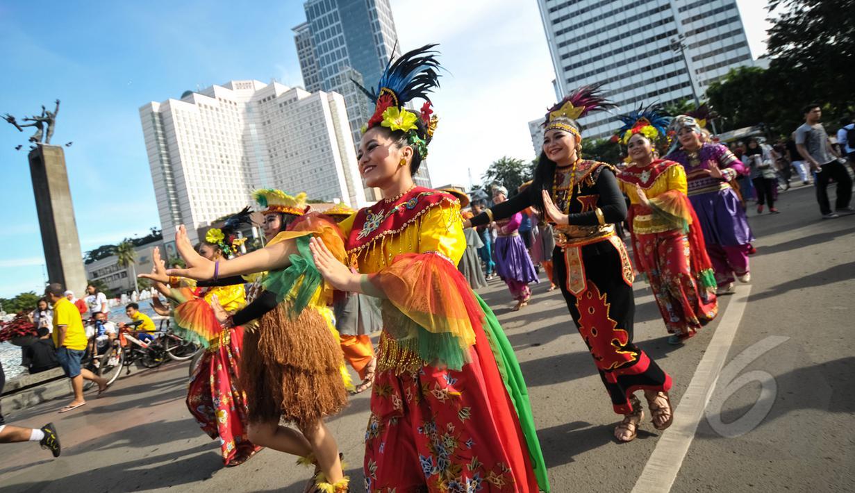 Kelompok seniman T-Ta asal Universitas Paramadina menari saat car free day di Bundara HI, Jakarta, Minggu (26/4/2015). Mereka meminta sumbangan kepada warga untuk mengikuti Interntional Folklore Festival di Spanyol. (Liputan6.com/Faizal Fanani)