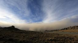 Badai pasir bergerak ke Zhangye di provinsi Gansu barat laut China (25/11). Menurut pemerintah setempat, sebuah kota di barat laut China ini dilanda badai pasir yang memicu kebakaran di pedesaan.  (AFP Photo/China Out)