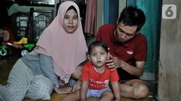 Fauziah Afiqa (tengah) berpose dengan ayah dan ibunya di kediamannya di Kampung Bulak Sentul, Harapan Jaya, Bekasi, Jawa Barat, Kamis (10/10/2019). Afiqa merupakan keturunan Betawi asli pasangan Ahmad Fauzi (26) dan Dian Irna Kurniawati (25). (merdeka.com/Iqbal Nugroho)
