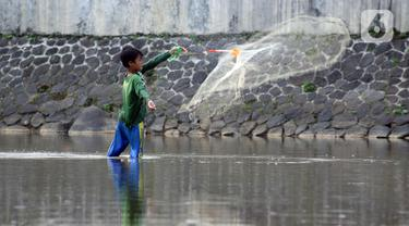 Seorang anak menjala ikan di area Bendung Katulampa, Kota Bogor, Jawa Barat, Senin (3/8/2020). Debit air sungai Ciliwung di Bendung Katulampa yang mengalami penyusutan sejak satu bulan terakhir dimanfaatkan anak-anak untuk bermain air dan layangan. (Liputan6.com/Helmi Fithriansyah)