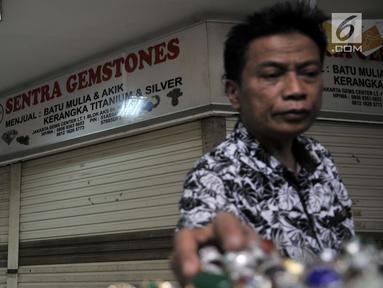 Pengunjung melihat koleksi batu akik di salah satu kios yang masih bertahan di Pasar Rawa Bening, Jakarta, Senin (10/9). Sepinya pembeli menyebabkan banyak kios pedagang batu akik tutup akibat gulung tikar. (Merdeka.com/Iqbal S. Nugroho)